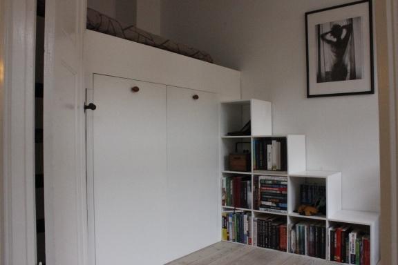 Sengen set fra stuen, bogreolen fungerer også som træppe